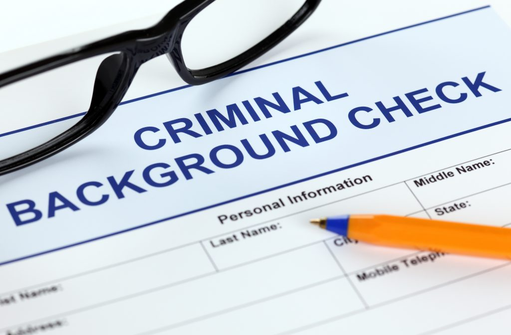 Criminal background check application form alongside pen and glasses for job applicants to fill out