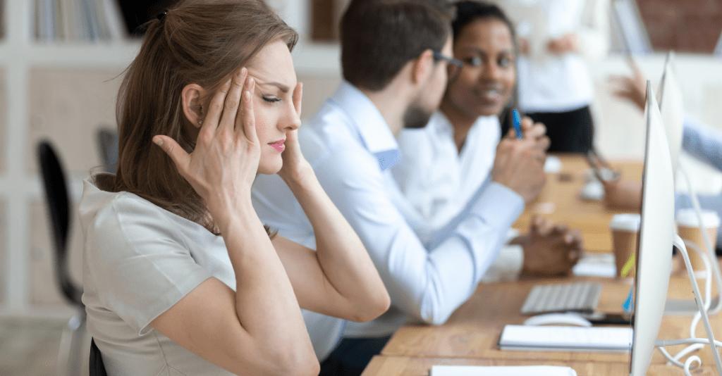 A female employee feeling overwhelmed at work.