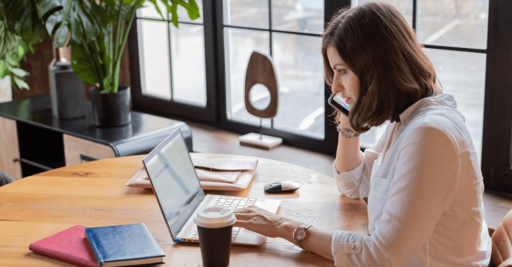 A woman works remotely from a cafe.