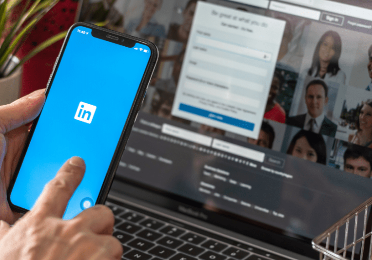 Hiring employer opens up LinkedIn app on phone to seek new potential employees.